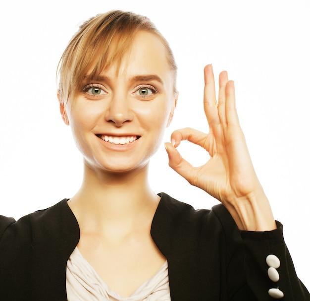Mulher de negócios jovem alegre sorridente feliz com um gesto de aprovação, sobre fundo branco
