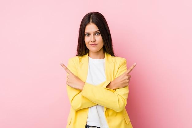 Mulher de negócios jovem aponta para o lado, está tentando escolher entre duas opções.