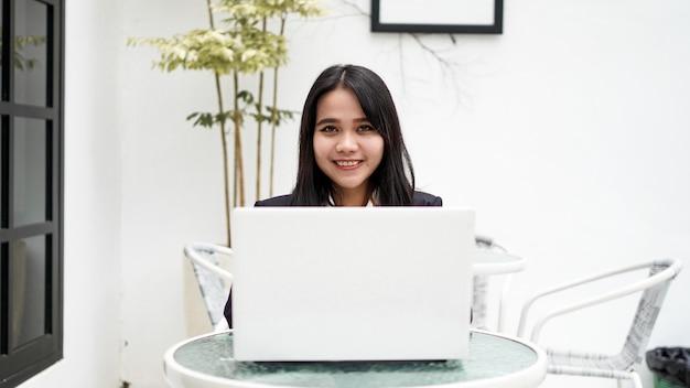 Mulher de negócios jovem asiática trabalhando em um computador no escritório