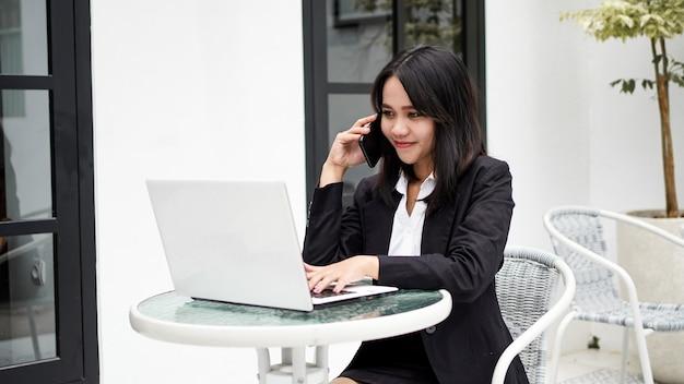 Mulher de negócios jovem asiática trabalhando no computador e falando no smartphone no escritório
