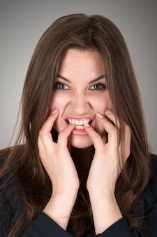 Mulher de negócios jovem assustada e estressada mordendo os dedos