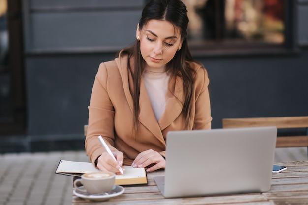 Mulher de negócios jovem atraente escrevendo algo no caderno. beber café feminino e trabalhar ao ar livre usando o laptop.