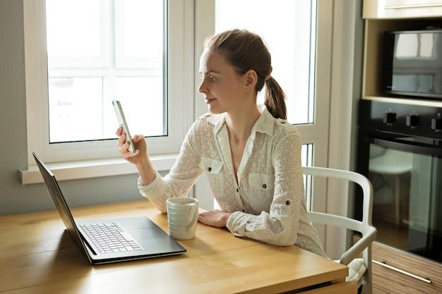 Mulher de negócios jovem atraente trabalhando com computador laptop na mesa de madeira em casa