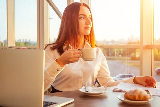 Mulher de negócios jovem bebe café e trabalha atrás do laptop com papéis.