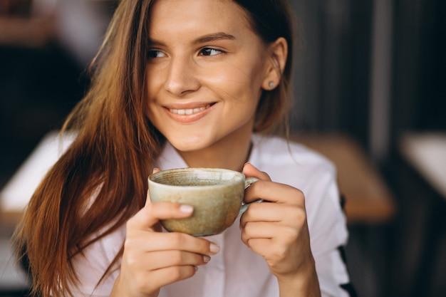 Mulher de negócios jovem bebendo café em um café