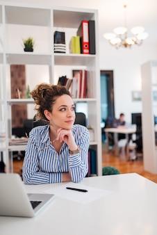 Mulher de negócios jovem bonita com cabelo encaracolado segurando óculos enquanto está sentado no local de trabalho