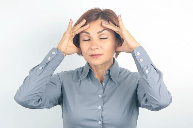 Mulher de negócios jovem bonita com os olhos fechados pensa sobre seu projeto em um branco.