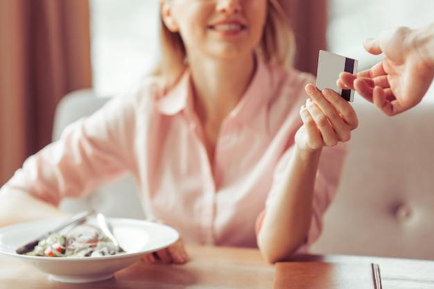 Mulher de negócios jovem bonita está pagando com um cartão de crédito.