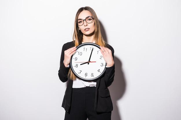 Mulher de negócios jovem bonita segurando nas mãos o relógio em branco
