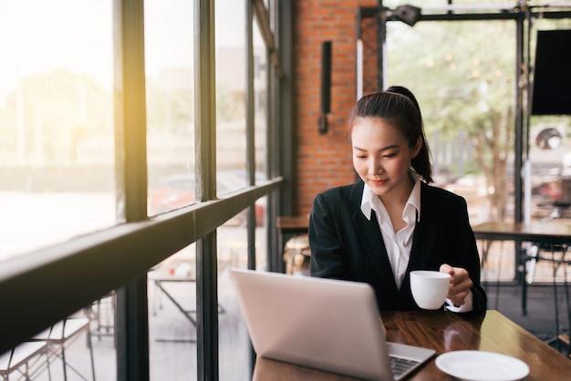 Mulher de negócios jovem bonita sentada à mesa e tomando notas