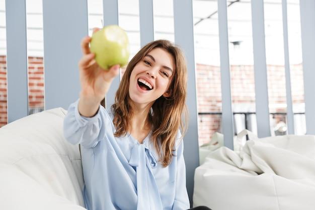 Mulher de negócios jovem bonita sentada em um sofá no escritório, mostrando maçã verde