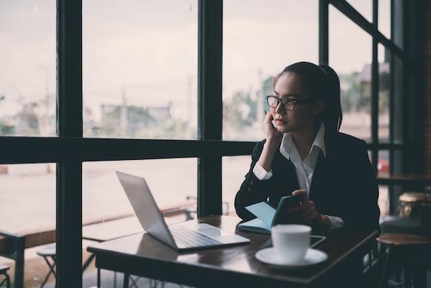 Mulher de negócios jovem bonita sentada na mesa e tomar notas. no café