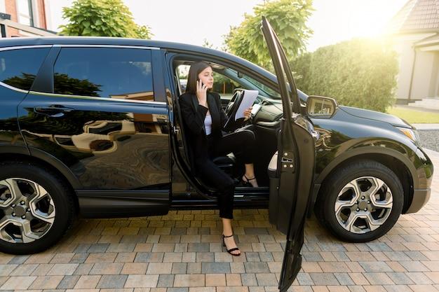 Mulher de negócios jovem bonita terno preto, usando telefone celular e fazendo anotações em papéis, enquanto está sentado no carro com a porta aberta