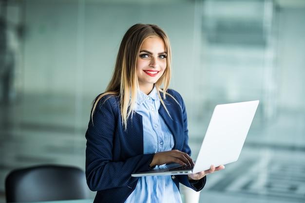 Mulher de negócios jovem bonita usando laptop em pé perto da mesa no escritório