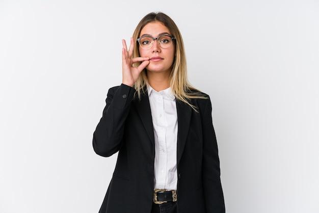 Mulher de negócios jovem caucasiana com os dedos nos lábios, mantendo um segredo.