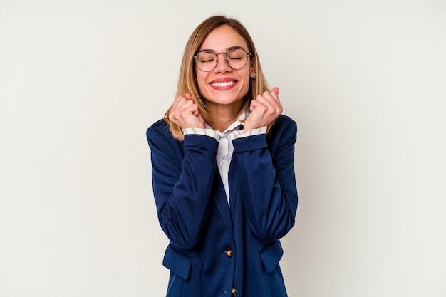 Mulher de negócios jovem caucasiana isolada no branco levantando o punho, sentindo-se feliz e bem sucedido. conceito de vitória.