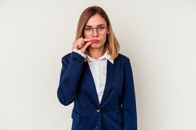 Mulher de negócios jovem caucasiana isolada no fundo branco com os dedos nos lábios, mantendo um segredo.