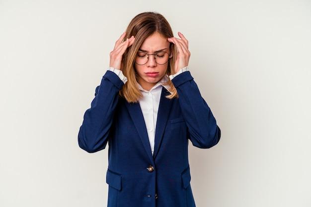 Mulher de negócios jovem caucasiana isolada no fundo branco, tocando as têmporas e tendo dor de cabeça.