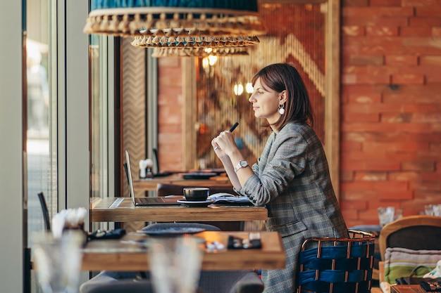 Mulher de negócios jovem com blazer cinza, sentado à mesa no café e escrevendo no caderno. freelancer, trabalhar numa cafetaria. aprendizagem online.