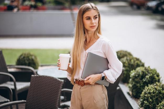 Mulher de negócios jovem com laptop tomando café fora do café