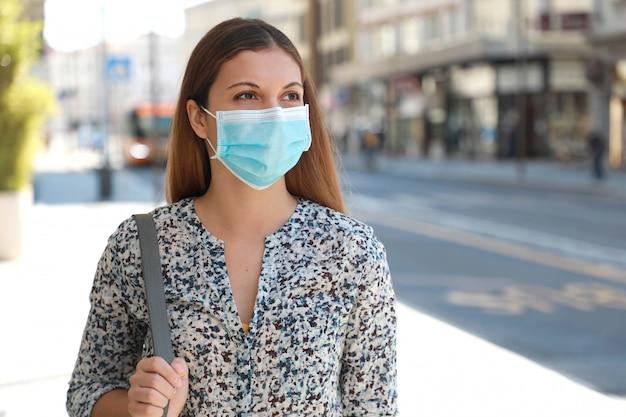 Mulher de negócios jovem com máscara cirúrgica esperando ônibus em parada de ônibus em rua da cidade