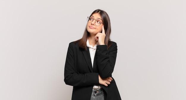 Mulher de negócios jovem com olhar concentrado, pensando com uma expressão duvidosa, olhando para cima e para o lado
