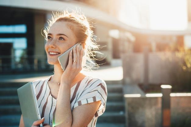 Mulher de negócios jovem com sardas e cabelo ruivo falando com alguém no telefone enquanto segura um computador sentado no banco