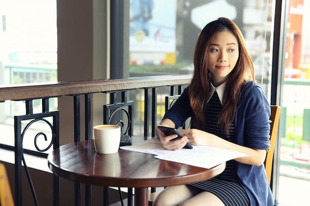Mulher de negócios jovem com smartphone e café