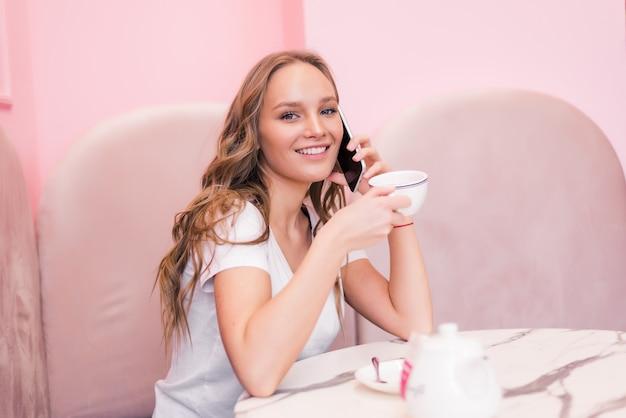 Mulher de negócios jovem com vestido cinza, sentada à mesa no café, falando no telefone oncell enquanto faz anotações no caderno