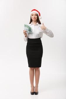 Mulher de negócios jovem conceito de natal e finanças mostrando dinheiro e polegar para cima