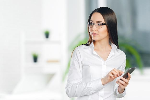 Mulher de negócios jovem, confiante, bem sucedida e bonita com o telemóvel isolado