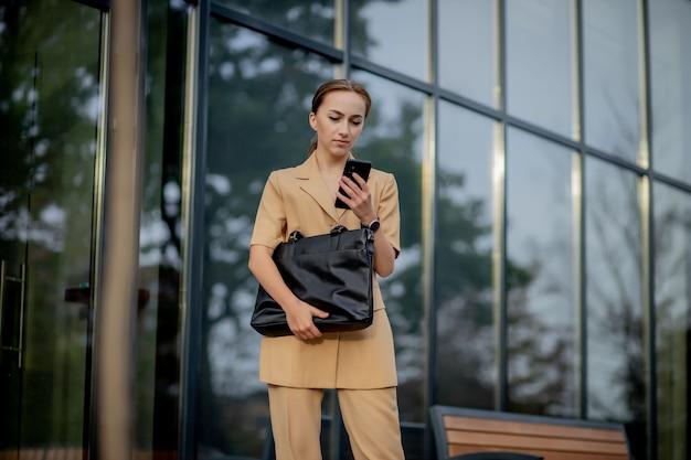 Mulher de negócios jovem confiante caucasiana adulta está falando ao telefone lá fora, perto de edifício de escritórios modernos.