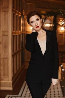 Mulher de negócios jovem confiante com maquiagem de noite e lábios vermelhos, usando um elegante terno preto posando no interior vintage