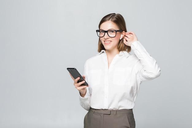 Mulher de negócios jovem, confiante e bonita falando via airpods, fone de ouvido sem fio segurando o telefone isolado na parede branca