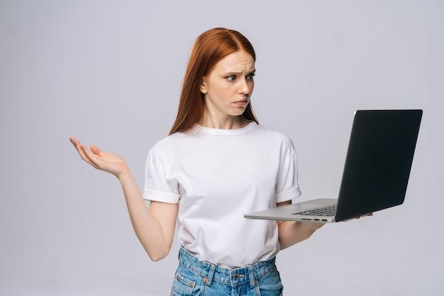 Mulher de negócios jovem confusa chocada segurando, mantendo o laptop aberto e olhando para a tela