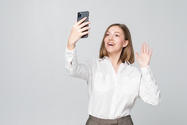 Mulher de negócios jovem cumprimentando alguém na chamada de vídeo no telefone na parede branca.