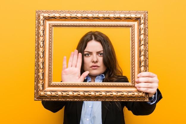 Mulher de negócios jovem curvilínea plus size segurando um quadro de pé com a mão estendida, mostrando o sinal de pare, impedindo-o.