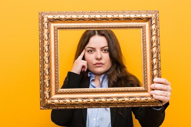 Mulher de negócios jovem curvilínea plus size segurando uma moldura apontando sua têmpora com o dedo, pensando, focada em uma tarefa.