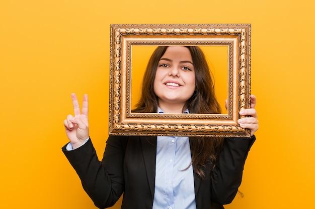 Mulher de negócios jovem curvilínea plus size segurando uma moldura mostrando o número dois com os dedos.
