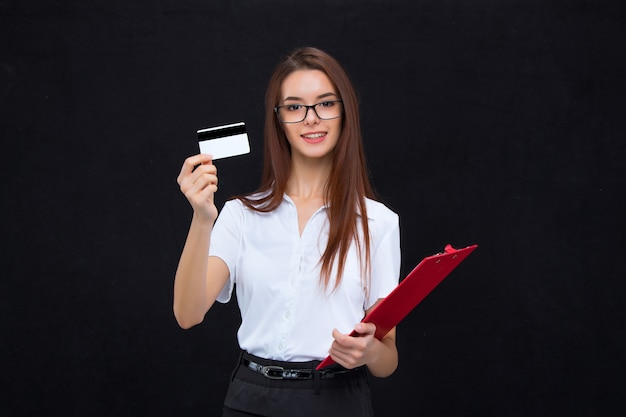 Mulher de negócios jovem de óculos com cartão de crédito e prancheta para anotações