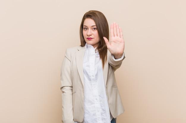 Mulher de negócios jovem de pé com a mão estendida, mostrando o sinal de stop, impedindo-o.