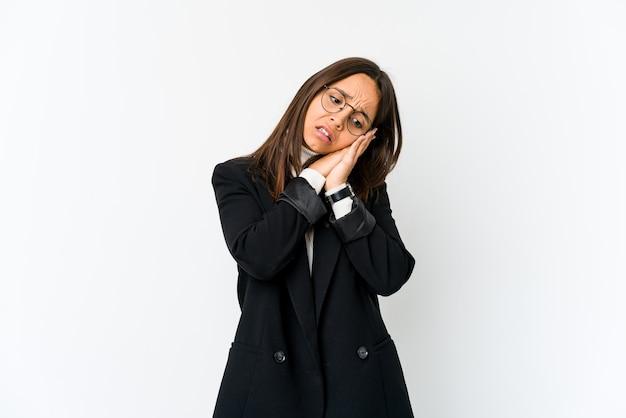 Mulher de negócios jovem de raça mista isolada na parede branca bocejando, mostrando um gesto cansado, cobrindo a boca com a mão.