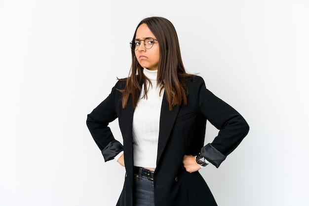Mulher de negócios jovem de raça mista isolada no fundo branco, rosto carrancudo em desgosto, mantém os braços cruzados.
