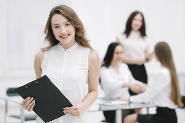 Mulher de negócios jovem de sucesso com a área de transferência no fundo do escritório.