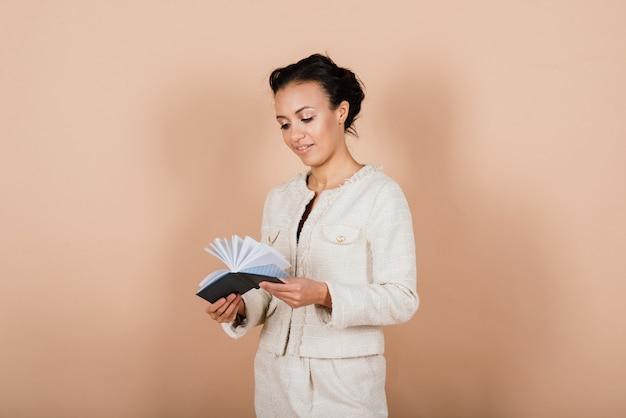 Mulher de negócios jovem de sucesso com as mãos postas sorrindo sobre um fundo cinza em estúdio
