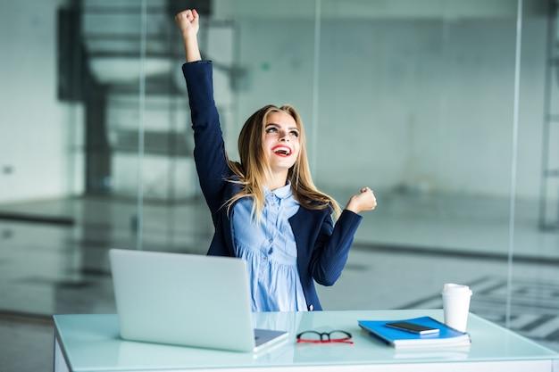 Mulher de negócios jovem de sucesso com os braços erguidos no escritório