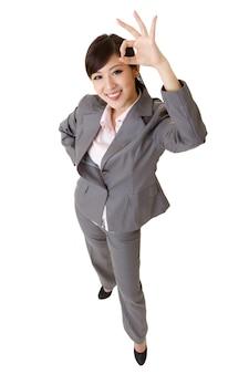 Mulher de negócios jovem e animada sorrindo e dando um sinal de ok