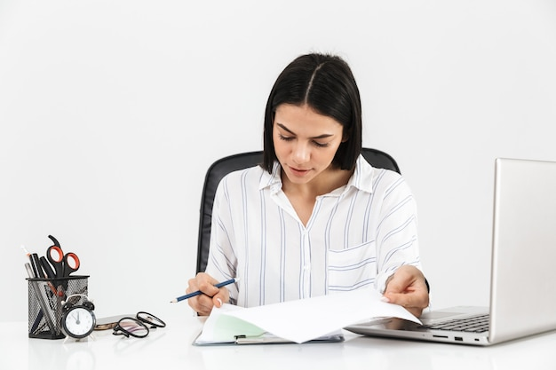 Mulher de negócios jovem e atraente sentada na mesa isolada na parede branca, trabalhando com um computador laptop e documentos