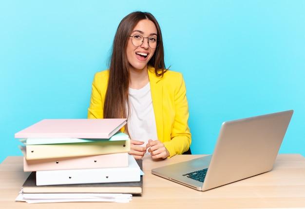 Mulher de negócios jovem e bonita com um sorriso grande, amigável e despreocupado, parecendo positiva, relaxada e feliz, arrepiante