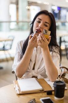 Mulher de negócios jovem e bonita corrigindo a maquiagem com batom e espelho sentado à mesa do café